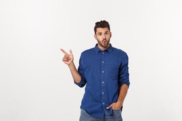 Portret van een opgewonden gelukkig man wijzende vinger weg op kopie ruimte.