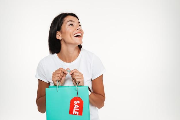 Portret van een opgewonden gelukkig mooie vrouw met boodschappentas