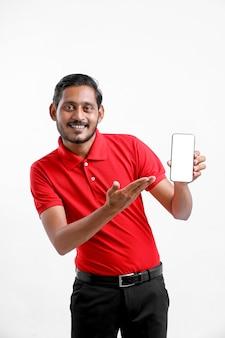 Portret van een opgewonden gelukkige jonge bezorger in een rood t-shirt en een smartphone op een witte achtergrond. Premium Foto