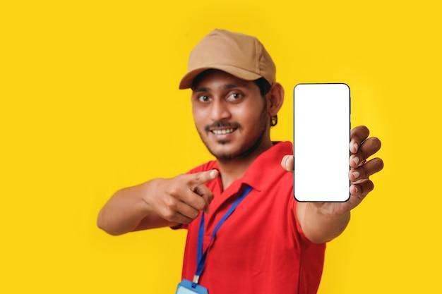 Portret van een opgewonden gelukkige jonge bezorger in een rood t-shirt en een smartphone op een witte achtergrond.