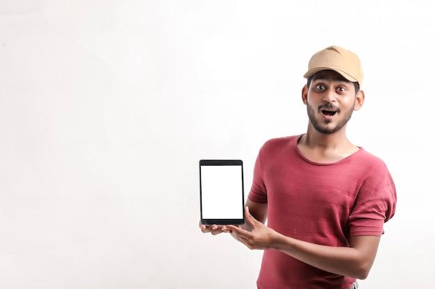 Portret van een opgewonden gelukkige jonge bezorger in pet die op een witte achtergrond staat. kijkende camera met weergave van mobiele telefoon.