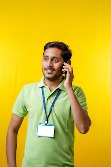 Portret van een opgewonden gelukkige jonge bezorger in t-shirt en smartphone tonen op gele achtergrond.