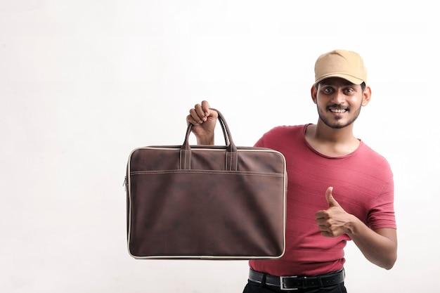 Portret van een opgewonden, gelukkige jonge bezorger met een pet die over een witte achtergrond staat en een tas in de hand houdt.