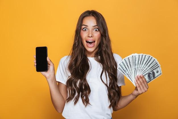 Portret van een opgewonden jong meisje met lang donkerbruin haar dat zich over gele muur bevindt, geldbankbiljetten houdt, leeg scherm mobiele telefoon toont
