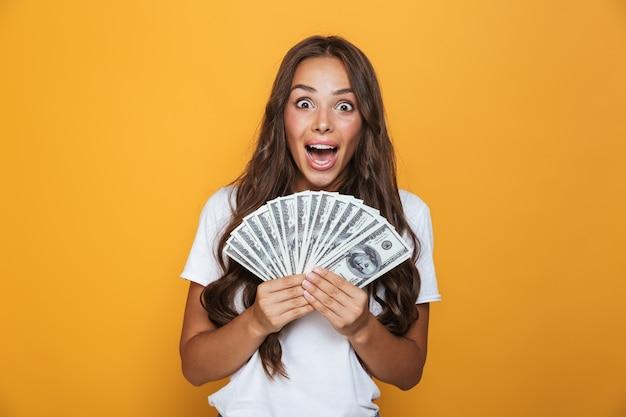 Portret van een opgewonden jong meisje met lang donkerbruin haar dat zich over gele muur bevindt, geldbankbiljetten houdt
