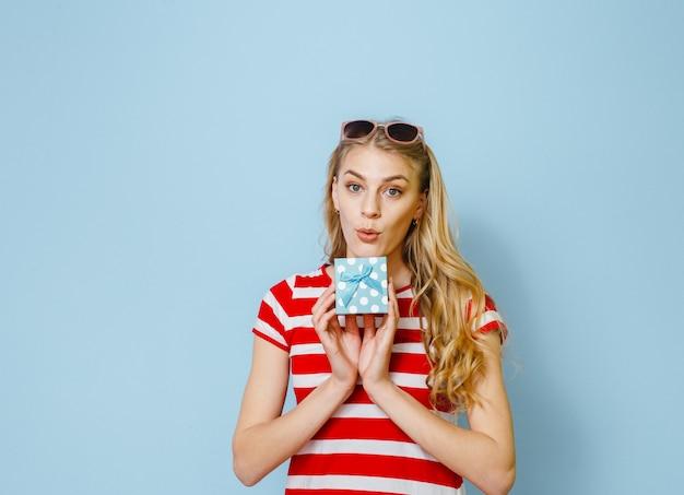 Portret van een opgewonden jong mooi blondemeisje die een gift houden en gelukkig over blauwe achtergrond