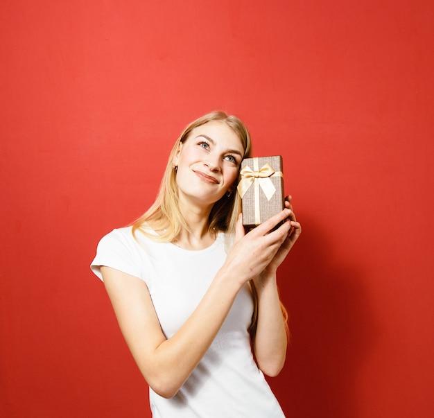 Portret van een opgewonden jong mooi blondemeisje die een gift houden en gelukkig over rode achtergrond