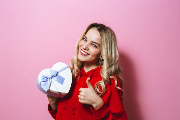 Portret van een opgewonden jong mooi blondemeisje die een gift houden en gelukkig over roze muur