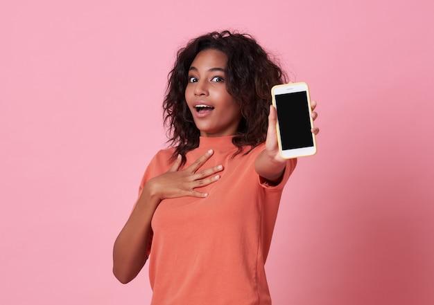 Portret van een opgewonden jonge afrikaanse vrouw die bij het lege scherm mobiele telefoon toont die over roze wordt geïsoleerd.