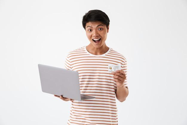 Portret van een opgewonden jonge aziatische laptop van de mensenholding