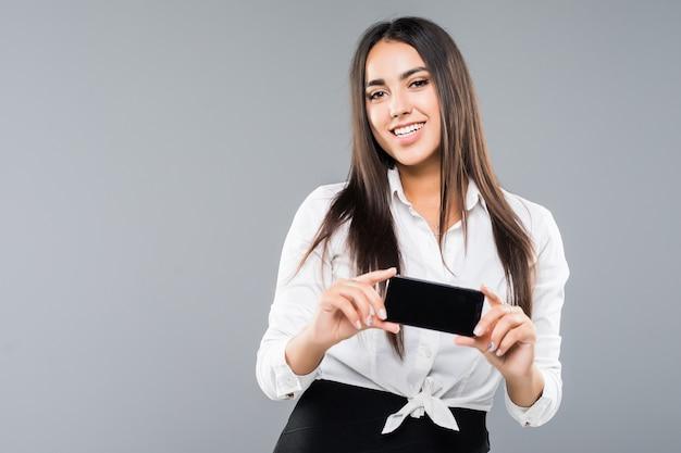 Portret van een opgewonden jonge bedrijfsvrouw die met lege het scherm mobiele telefoon richt die op wit wordt geïsoleerd
