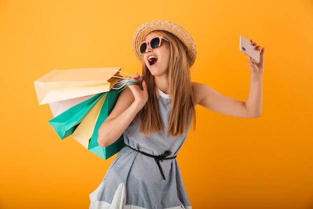 Portret van een opgewonden jonge blonde vrouw in zomerhoed
