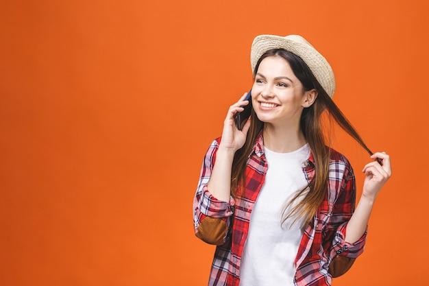 Portret van een opgewonden jonge brunette vrouw in zomer hoed en casual met behulp van mobiele telefoon geïsoleerd op oranje achtergrond.