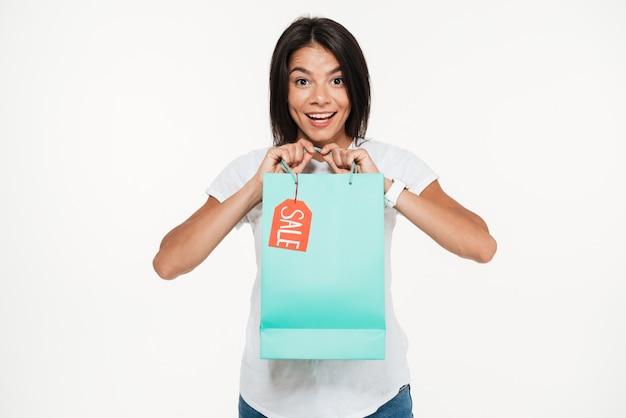 Portret van een opgewonden jonge de verkoop van de vrouwenholding het winkelen zak