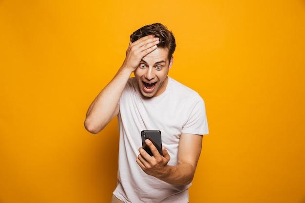 Portret van een opgewonden jonge man die mobiele telefoon bekijkt