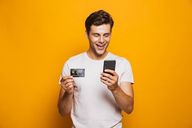 Portret van een opgewonden jonge man met mobiele telefoon