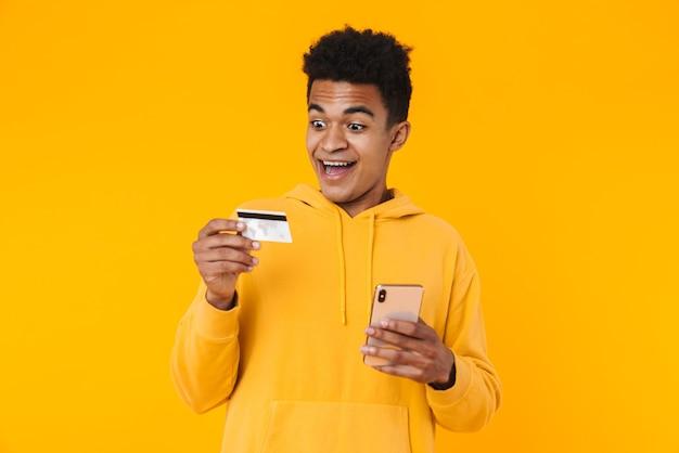 Portret van een opgewonden jonge tienerjongen die geïsoleerd over een gele muur staat en een creditcard toont tijdens het gebruik van een mobiele telefoon