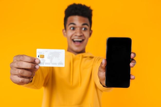 Portret van een opgewonden jonge tienerjongen die geïsoleerd over een gele muur staat, met een creditcard en een lege mobiele telefoon