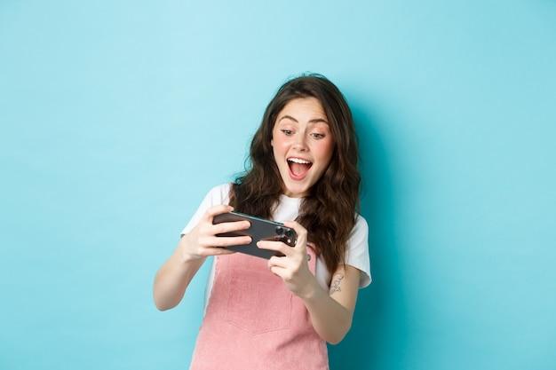 Portret van een opgewonden jonge vrouw die een mobiel videogame met beide handen speelt, geamuseerd lacht, naar het scherm kijkt en over een blauwe achtergrond staat.