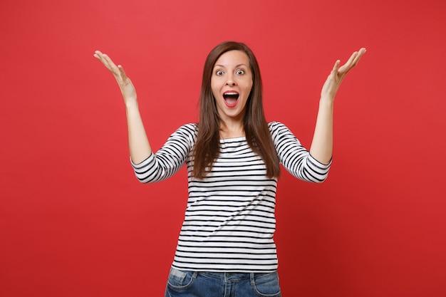 Portret van een opgewonden jonge vrouw die handen spreidt en de mond wijd open houdt, verbaasd kijkend?