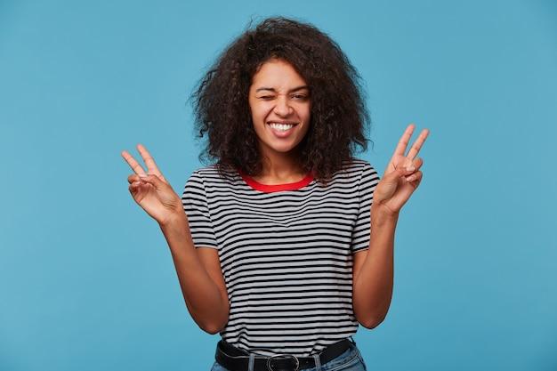 Portret van een opgewonden jonge vrouw die vredesgebaar toont