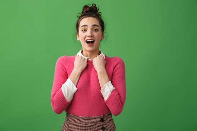 Portret van een opgewonden jonge vrouw schreeuwen geïsoleerd over groen