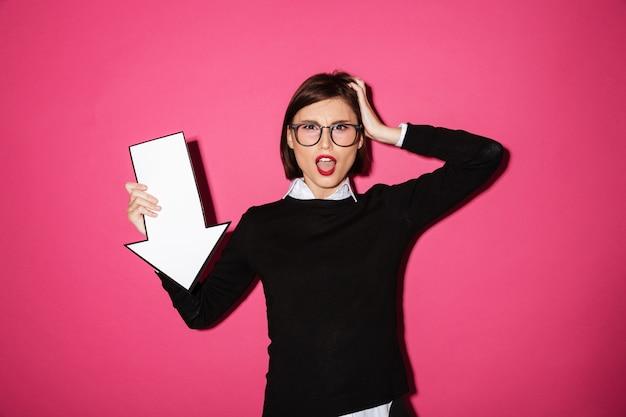 Portret van een opgewonden jonge zakenvrouw met pijl naar beneden wijst
