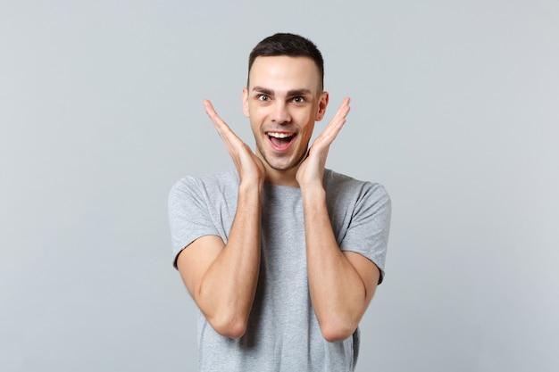 Portret van een opgewonden jongeman in vrijetijdskleding die zijn mond openhoudt en zijn handen in de buurt van zijn gezicht spreidt