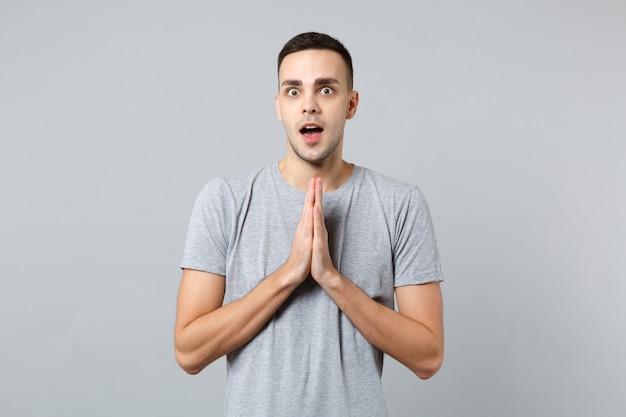 Portret van een opgewonden jongeman in vrijetijdskleding die zijn mond openhoudt, zijn handen gevouwen en biddend