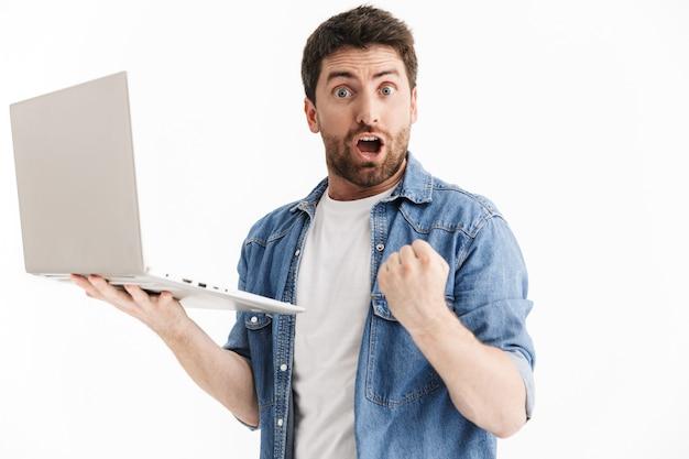 Portret van een opgewonden knappe bebaarde man met vrijetijdskleding die geïsoleerd staat, met behulp van een laptopcomputer