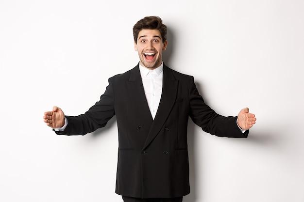Portret van een opgewonden knappe man in pak, vormgevend groot object op kopieerruimte en glimlachend verbaasd, iets vasthoudend, staande op een witte achtergrond