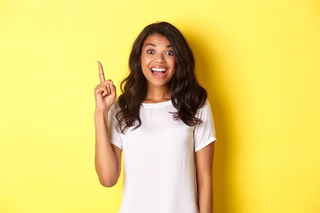 Portret van een opgewonden lachende afro-amerikaanse vrouw met een idee die vinger opsteekt en haar sugge... Premium Foto