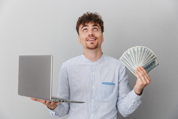 Portret van een opgewonden man gekleed in een shirt glimlachend terwijl hij een zilveren laptop vasthoudt en een hoop geld cash geïsoleerd over een grijze muur