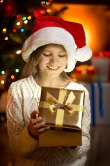 Portret van een opgewonden meisje dat in een glinsterende geschenkdoos kijkt