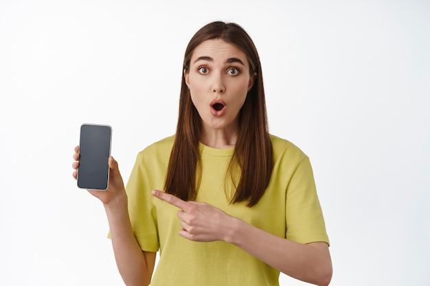 Portret van een opgewonden meisje dat naar het scherm van de smartphone wijst, interface mobiele telefoon-app toont, winkeltoepassing aanbeveelt, staande op wit.