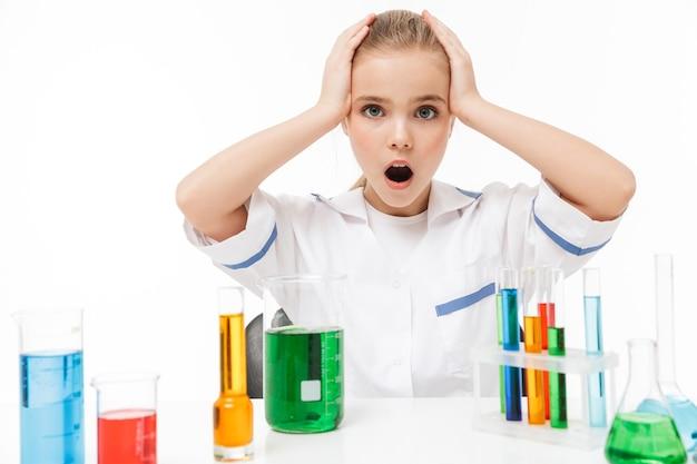Portret van een opgewonden meisje in een witte laboratoriumjas die chemische experimenten maakt met veelkleurige vloeistof in reageerbuizen geïsoleerd over een witte muur