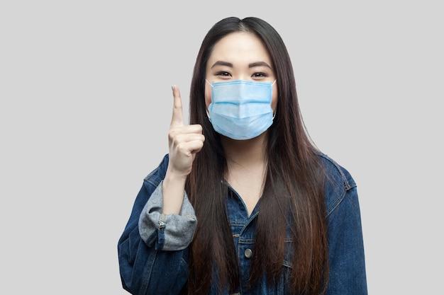 Portret van een opgewonden, mooi brunette aziatisch meisje met een chirurgisch medisch masker in een blauwe spijkerjas die staat en naar de camera kijkt, vinger omhoog. indoor studio opname, geïsoleerd op een grijze achtergrond.