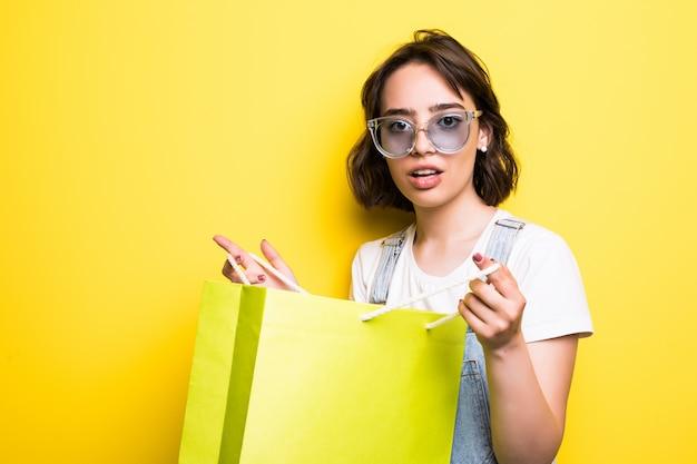 Portret van een opgewonden mooi meisje die in zonnebril dragen die boodschappentassen geïsoleerd houden