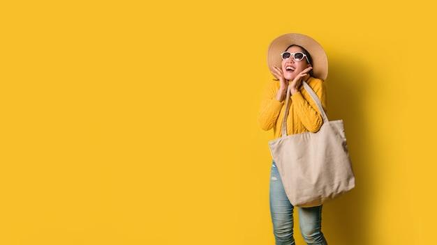 Portret van een opgewonden mooi meisje die kleding en zonnebril dragen die het winkelen zakken houden.