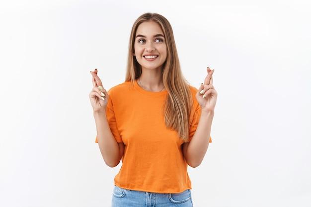 Portret van een opgewonden, optimistisch, gelukkig blond meisje dat de vingers kruist en wegkijkt, wachtend op goed nieuws, biddend of smekend
