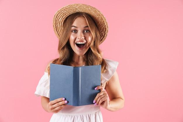 Portret van een opgewonden verraste schattige jonge mooie vrouw die zich voordeed over een roze muurleesboek met geopende mond.
