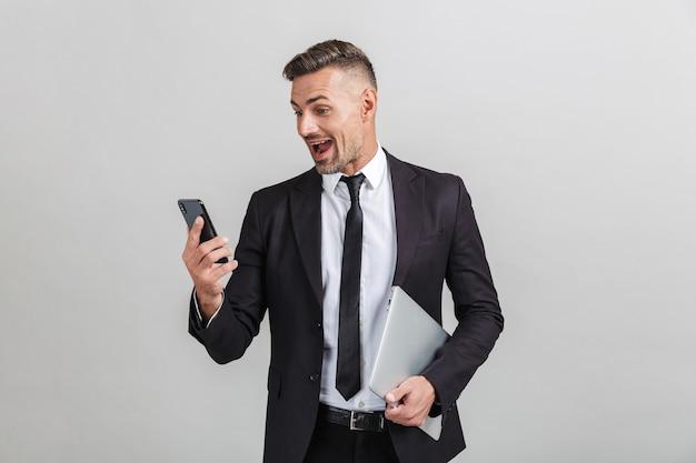 Portret van een opgewonden volwassen zakenman in een kantoorpak die naar een smartphone kijkt en een laptop vasthoudt terwijl hij geïsoleerd staat
