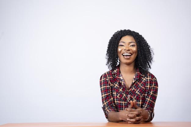 Portret van een opgewonden vrij jonge zwarte vrouw die aan een bureau zit