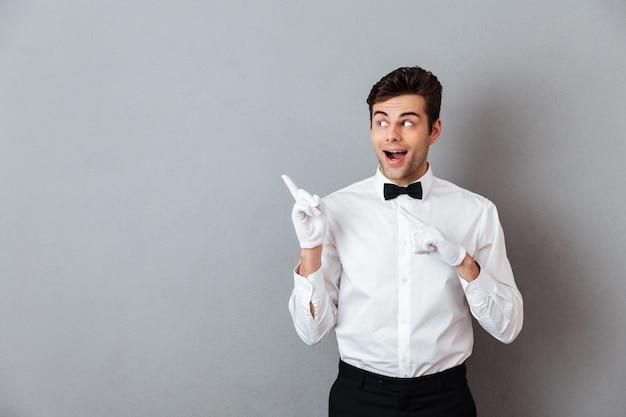 Portret van een opgewonden vrolijke mannelijke ober