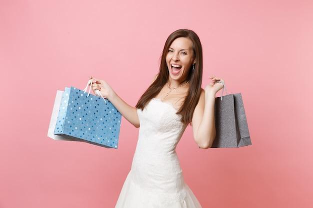 Portret van een opgewonden, vrolijke vrouw in witte kanten jurk met veelkleurige pakketten met aankopen na het winkelen