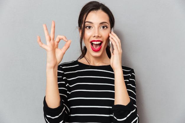 Portret van een opgewonden vrouw die op mobiele telefoon spreekt