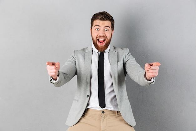Portret van een opgewonden zakenman gekleed in pak staande