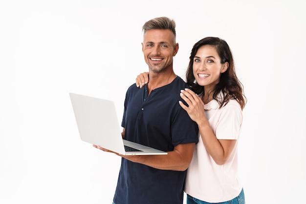 Portret van een optimistisch vrolijk volwassen verliefde paar geïsoleerd over witte muur met behulp van laptopcomputer.