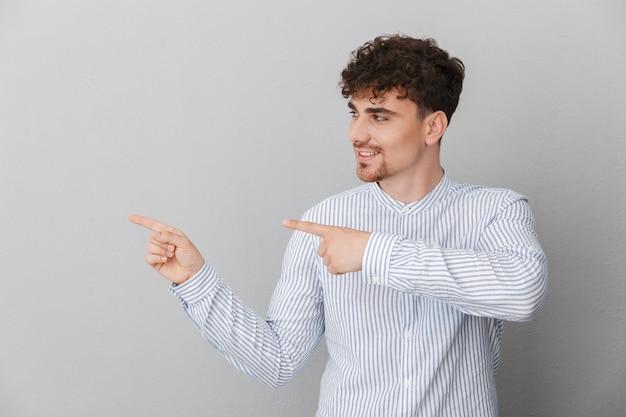 Portret van een optimistische gekrulde man gekleed in een shirt glimlachend en wijzend met de vingers opzij naar copyspace geïsoleerd over grijze muur