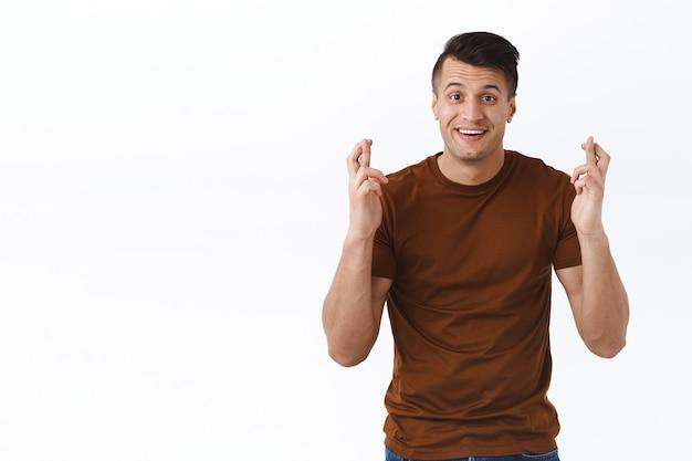 Portret van een optimistische, glimlachende knappe man die bidt voor een droom die uitkomt, anticiperend op goed nieuws, fortuin aan zijn kant, kruis vingers veel geluk